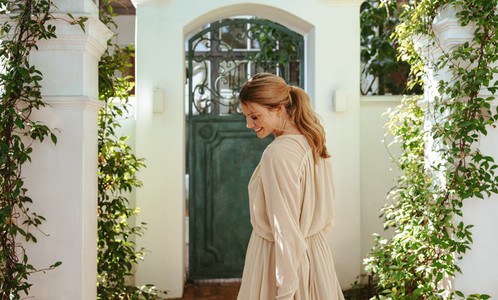 Cheerful young woman standing outside a luxury holiday home