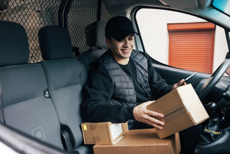 Smiling courier sitting on a drivers seat checking delivery information on mobile phone while holding box