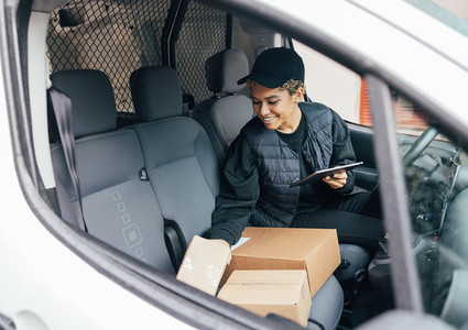 Smiling woman sitting on drivers seat checking packages and holding a digital tablet