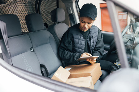 Woman in a uniform of a delivery company checking information on a digital tablet while sitting on drivers seat