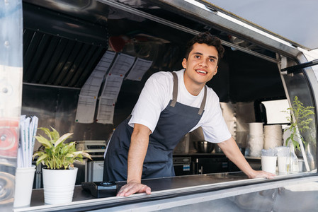 Young food truck owner in apron  Salesman looking away
