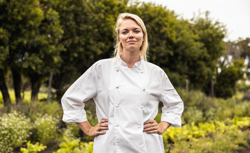 Chef standing with her arms crossed in a farm field