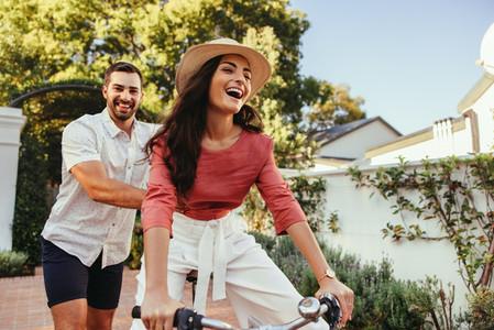 Young man pushing his girlfriend on a bike