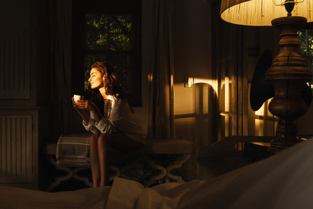 Beautiful young woman enjoying a cup of coffee in her hotel room
