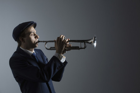 Young male musician playing trumpet on gray background