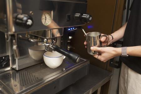 Barista steaming milk at espresso machine in cafe