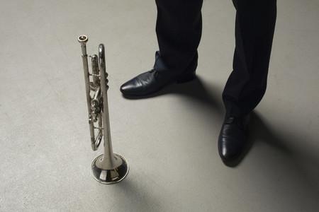 Man standing next to trumpet