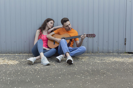 Young couple playing guitar at wall