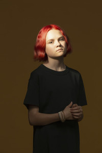 Portrait confident serious teenage girl with dyed red hair