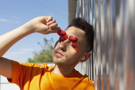 Serene young man removing sunglasses