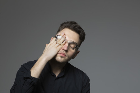 Tired young man rubbing eyes