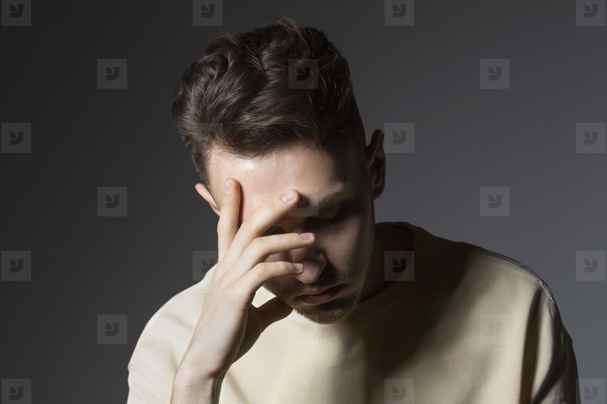 Tired young man with head in hands