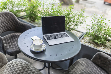 Laptop and cappuccino on patio table