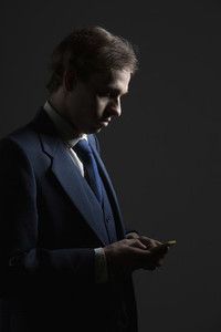 Businessman in suit texting with smart phone on black background