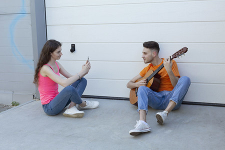 Young woman photographing boyfriend playing guitar in driveway