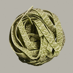 Close up uncooked spinach pasta noodle bundle on gray background