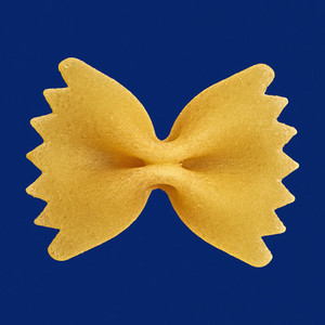 Close up uncooked farfalle bowtie pasta noodle on blue background