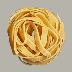 Close up uncooked pasta nest on gray background
