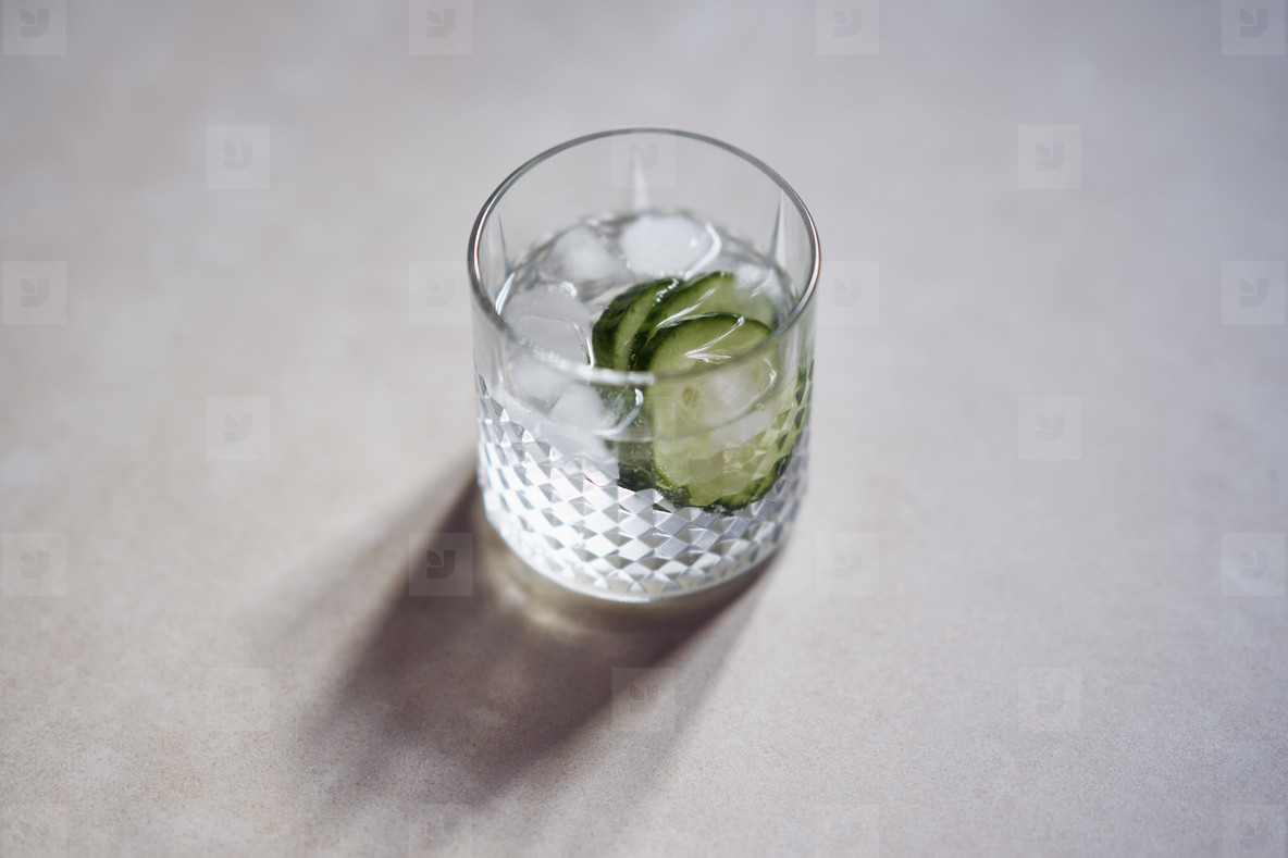 Glass of ice water with cucumber slices