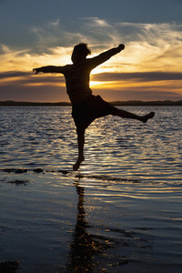 Silhouette boy jumping in ocean surf at sunset