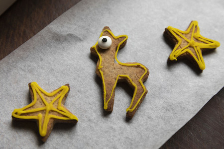 Decorated gingerbread reindeer and stars on parchment paper