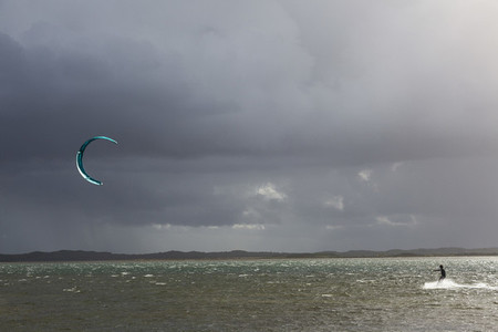 Kite boarder on ocean below stormy cloudy sky