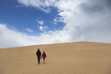 Mother and son walking along remote sand dunes