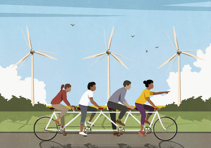 Friends riding tandem bicycle along idyllic field with wind turbines