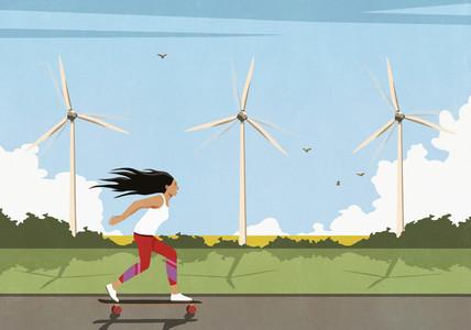 Carefree woman skateboarding along wind turbines in sunny field