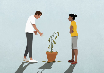 Unhappy couple looking at dead houseplant