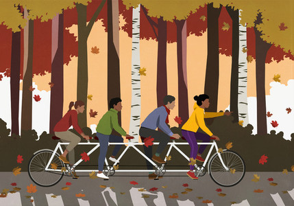 Friends riding tandem bicycle in autumn park