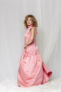 Portrait beautiful woman in pink satin dress against white background
