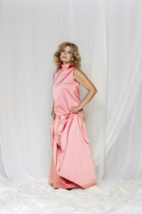 Portrait stylish beautiful woman in pink satin dress on white background