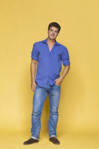 Portrait confident man in blue against yellow background