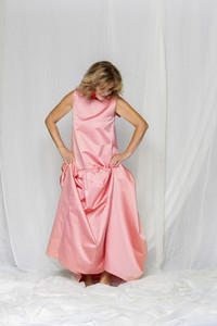 Woman in pink satin dress looking down