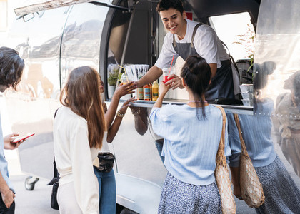 Smiling salesman giving beverages to customers while standing in food truck