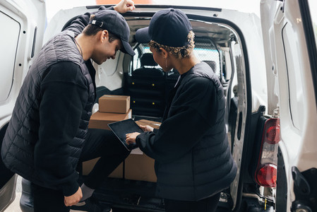 Delivery guys looking on digital tablet at car trunk checking information