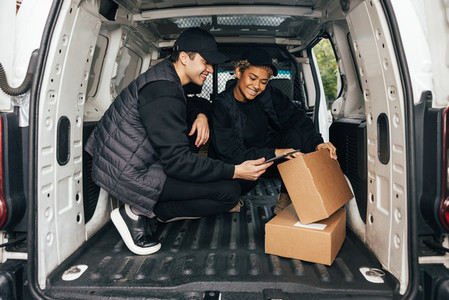 Two smiling couriers sitting in delivery van checking information on a box using digital tablet