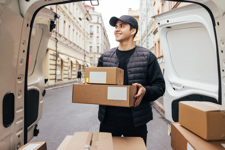 Male courier in uniform standing at van trunk holding boxes preparing for delivery to customer