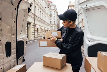 Woman in uniform holding packages while standing at car trunk  Courier preparing parcels for delivery