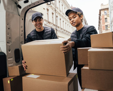 Two workers of delivery company loads cardboard boxes into a van