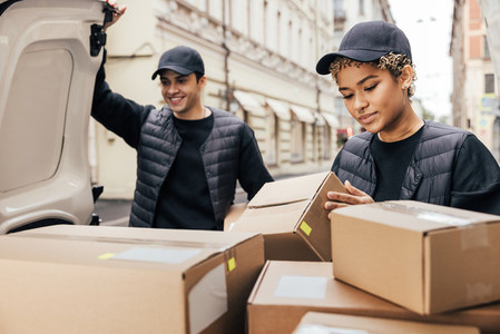 Two delivery people working at van trunk  Woman checking information on parcel