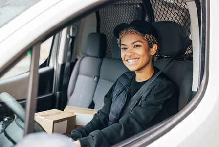 Portrait of a smiling woman working for delivery company sitting in a car looking away