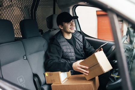 Male courier sitting on drivers seat with cardboard boxes and digital tablet looking away
