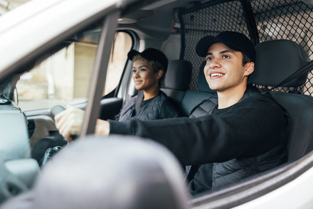 Two delivery coworkers sitting in van  Smiling courier driving a car