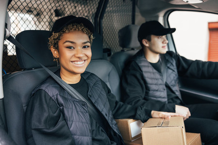 Smiling woman in uniform sitting in delivery van and looking at camera while her coworker driving