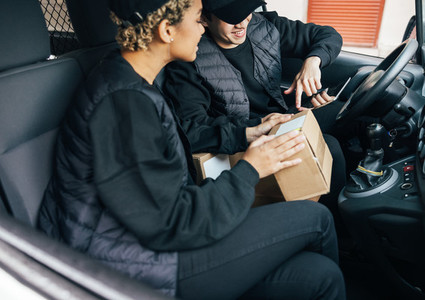 Two delivery coworkers in uniform checking information on cardboard box for shipment