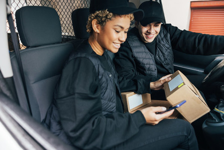 Two couriers sitting in car checking information on box using mobile phone