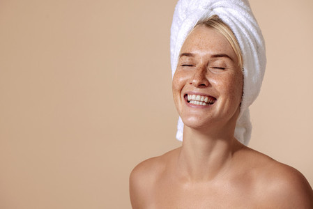 Portrait of a happy woman with freckles wrapped her hair with a white towel