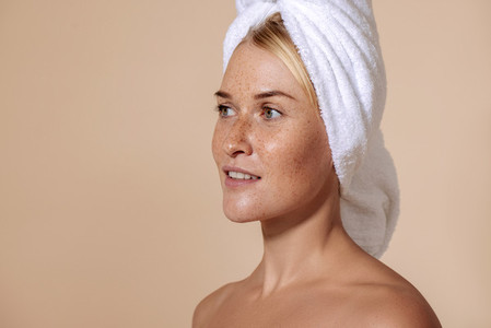 Portrait of young confident woman with freckles  Studio shot of a beautiful female with a towel on her head